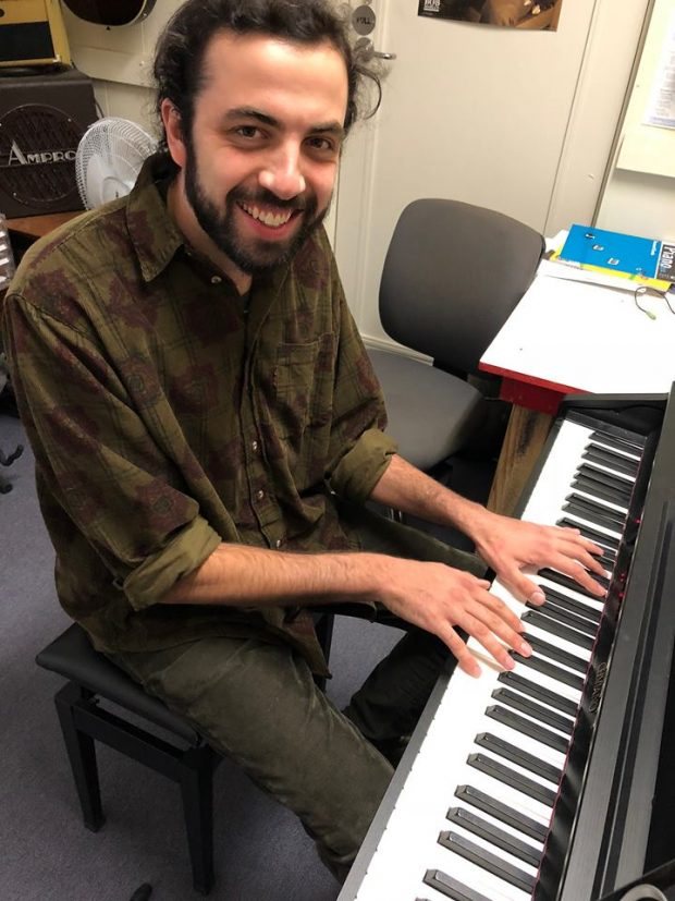A man wearing an olive green shirt seated at a piano